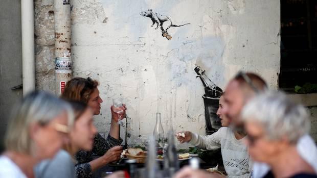 In einem Pariser Restaurant fliegt eine Banksy-Ratte auf einem Sektkorken über die Köpfe der Menschen hinweg