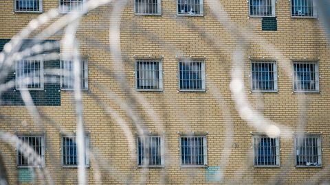 Fenster eine JVA im Hintergrund, Stacheldraht im Vordergrund