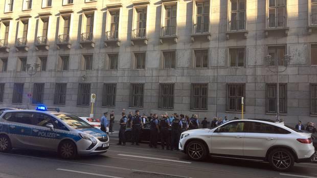 Ein Polizeiwagen mit Blaulicht und ein weißer SUV stehen auf einer Berliner Hauptstraße Kühlerhaube an Kühlerhaube