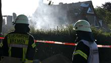 Bremen: Feuerwehrmänner schauen auf das noch rauchende Wohnhaus, das bei einer Explosion zerstört wurde.
