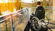 Ein Junge sitzt im Rollstuhl und schaut auf einen See