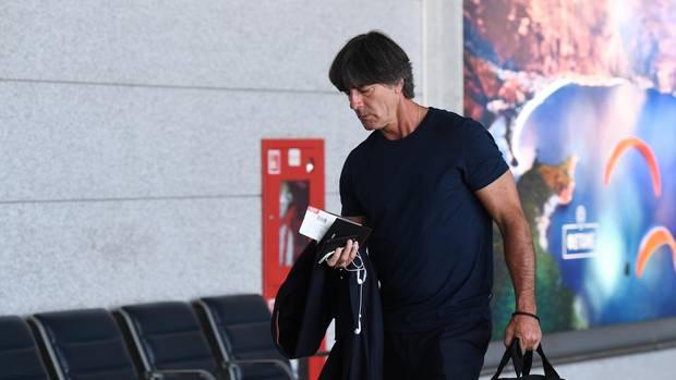 Bundestrainer Joachim Löw geht mit gesenktem Kopf und einer Tasche in der linken Hand zum Flieger aus Russland nach Frankfurt