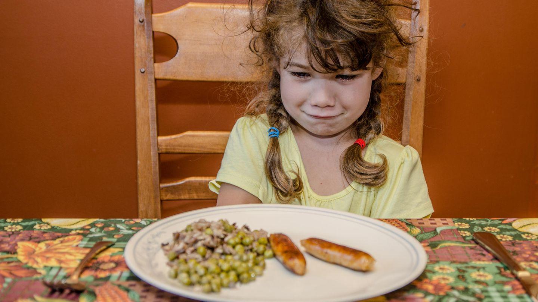Ein Mädchen sitzt am Tisch und guckt angewidert auf den Teller vor sich