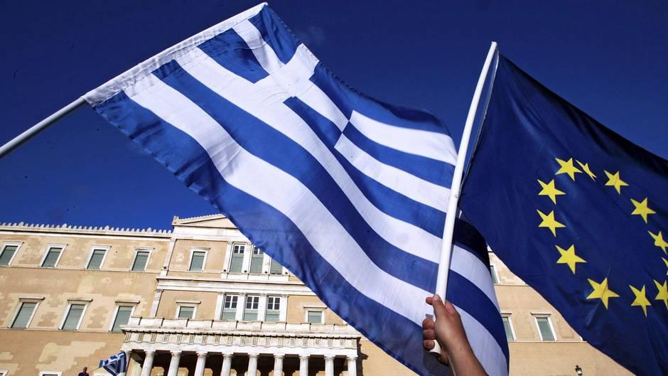 Griechische Flagge und und EU-Fahne vor demParlamentsgebäude in Athen