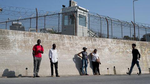 Gruppe von Migranten an der Mauer eines Flüchtlingslagers