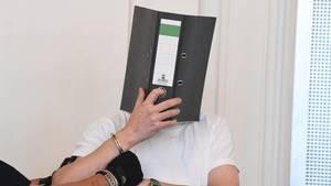 Der 44 Jahre alte Angeklagte im Missbrauchsprozess verdeckt bei der Verhandlung im Landgericht sein Gesicht