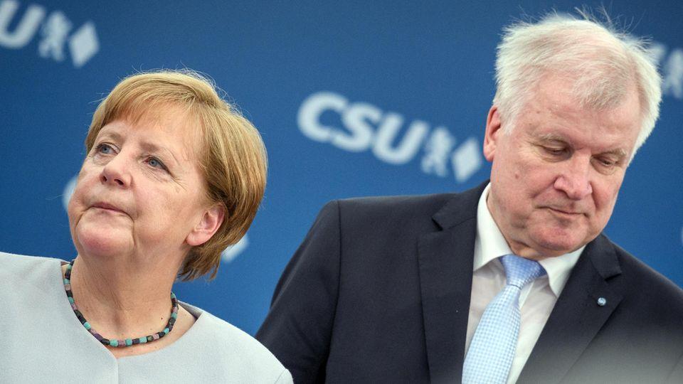 Bundeskanzlerin Angela Merkel (CDU) und Innenminister Horst Seehofer (CSU) stehen nebeneinander, schauen voneinander weg