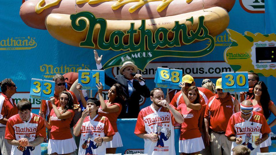 Joey Chestnut (Mitte, rechts) und Matt Stonie (Mitte, links) beim Hotdog-Wettessen. Der Kalifornier Chestnut gewann damals mit 70 Würstchenbroten und machte damit seinem Ruf als Champion alle Ehre.