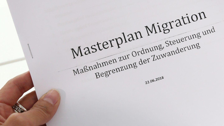 """Eine linke Frauenhand hält einen Ausdruck des """"Masterplans Migration"""" der CSU"""