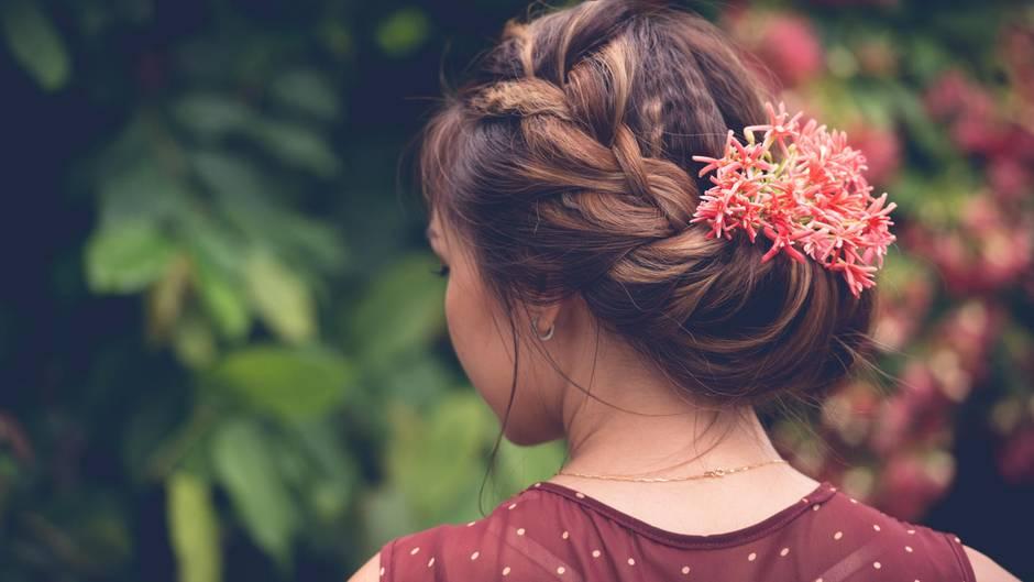 Mädchen von hinten mit Blumen im Haar