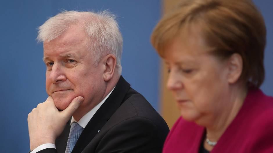 Horst Seehofer schaut skeptisch und stützt sich auf sein Kinn, Angela Merkel schaut auf den Tisch vor sich