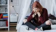 Eine Frau sitzt auf einem Bett und weint