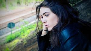 junge Frau guckt nostalgisch aus einem fenster