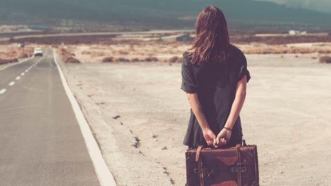 Eine Frau steht mit Koffer am Straßenrand