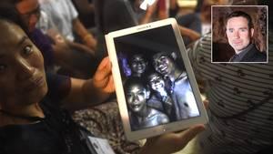 Ein Mutter zeigt ein Bild der in einer Höhle in Thailand gefundenen Jungen. Höhlenretter Martin Groß erwartet, dass sich die Rettung hinziehen wird.