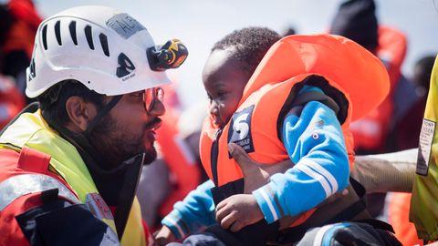 """Ein """"Sea-Watch""""-Mitarbeiter hilft einem Kleinkind im Mittelmeer"""