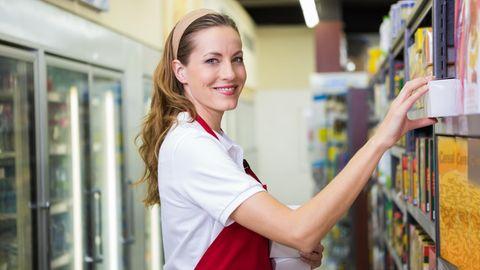 Eine junge Frau räumt ein Supermarkt-Regal ein