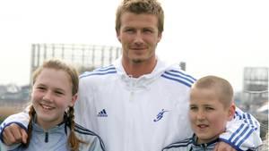 David Beckham (M.) gemeinsam mit Katie Goodland und Harry Kane im März 2005