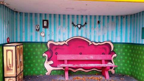 """Warten unterm Hirschgeweih  Früher war nicht alles besser, davon kann die Bushaltestelle in der Bahnhofstraße in Hückeswagen ein Liedchen röhren. Jahrelang kam sie im allerfeinsten Gammelgrau daher, bevor sie in zartem Violett errötete, über Nacht, ausgeführt von unbekannter Hand. """"Illegal!"""", urteilte die Stadtverwaltung und engagierte Graffiti-Künstler. Jetzt wartet man in Hückeswagen im Wohnzimmer auf den Bus. Nur die Bank, die ist hart wie eh und je. Und die Blätter weht's direkt unters Hirschgeweih."""