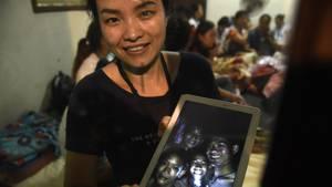 Die Mutter von einem der zwölf eingeschlossenen Jungenzeigt ein Bild ihres Sohnes mit seinen Freunden