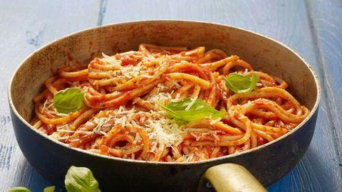 Spaghetti in Tomatensauce mit Käse und Basilikumblättern oben drauf.