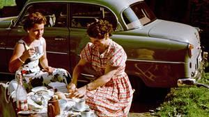 EinUrlaubsfoto aus Italien:Mutter und Tochterbei einem Picknick neben dem privaten Pkw in Meran.