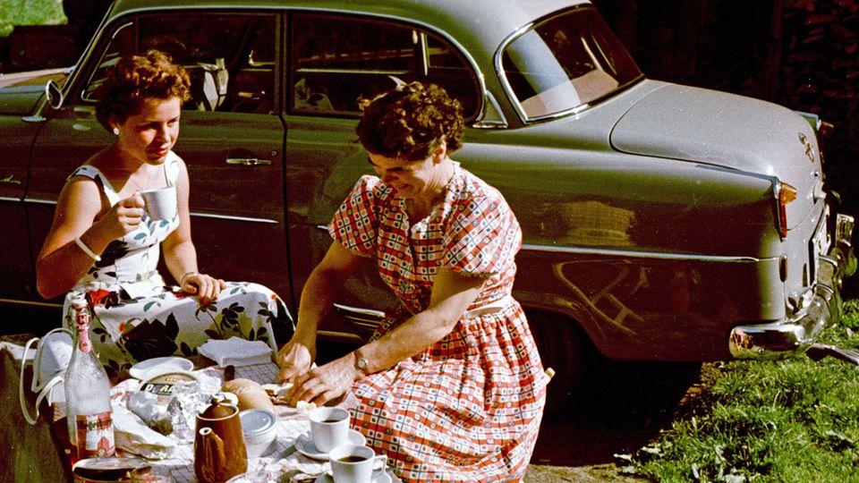 Urlaubsfoto auf dem Weg nach Süden:Mutter und Tochterbei einem Picknick neben dem privaten Pkw in Meran.