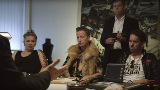 Eine Frau und zwei Männer sitzen an einem Tisch. Hinter ihnen steht ei n Bodyguard mit Gewehr