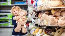 Kleines Mädchen mit Teddy-Bären im Arm am Supermarkt-Regal.