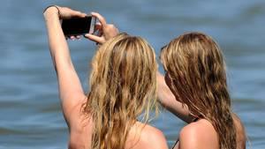 Zwei jungen Frauen machen in der Nordsee im Wasser ein Selfie.