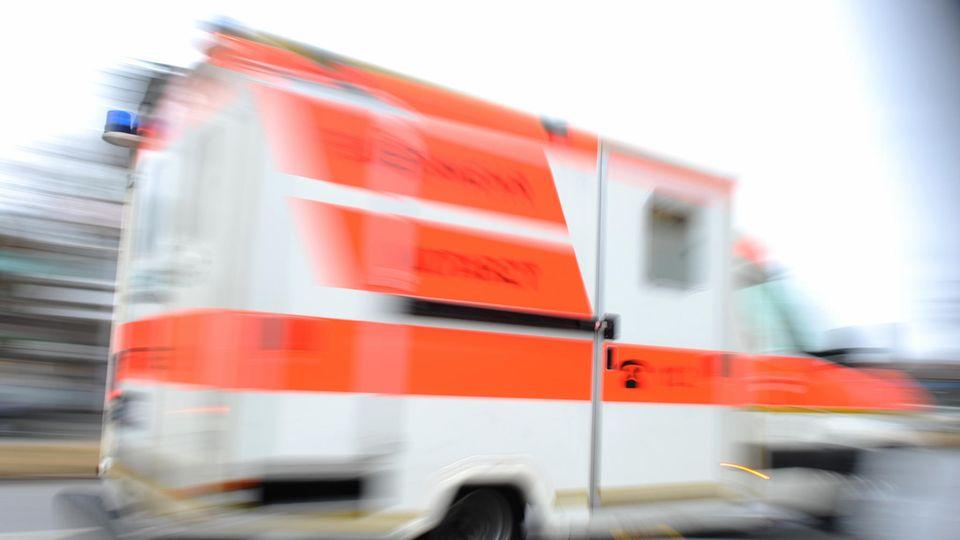 Ein weißer Krankenwagen mit orangenen Reflektorstreifen fährt schnell vorbei