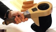 Eine Hand hält während einer Pressekonferenz einen Digitalen Klingelbeutel