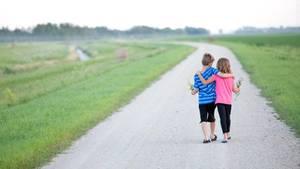 Zwei Kinder spazieren Arm in Arm über einen Weg