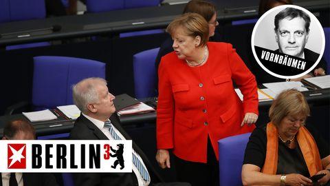 Im Bundestag steht Angela Merkel im roten Blazer vor Horst Seehofer, der auf seinem blauen Stuhl sitzt