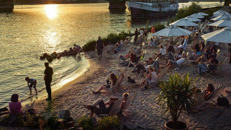 Am Rheinufer in Mainz-Kastel entspannen die Menschen auf Liegestühlen in der Abendsonne