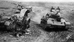 Eine Kolonne T-34 fährt an einem zerstörten Panzer IV vorbei.