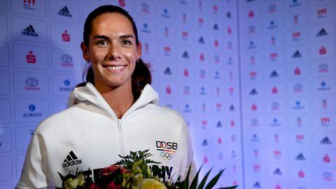Beachvolleyballerin Kira Walkenhorst steht in weißer Trainingsjacke und mit Blumenstrauß in den Händen vor einer Wand mit Logos