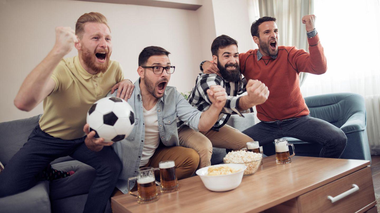 Freunde jubeln beim Fußball gucken