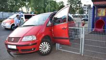 Ein roter VW hängt mit offener, nach vorne abgeknickter Fahrertür an der Ecke eines Metallzauns fest