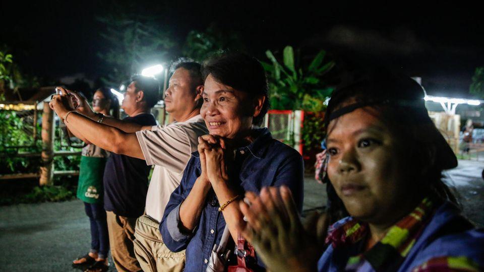 Zuschauer klatschen, als einer der geretteten Jungs in einem Krankenwagen abtransportiert wird
