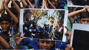Indische Schulkinder halten Fotos der eingeschlossenen Jungs in Thailand hoch