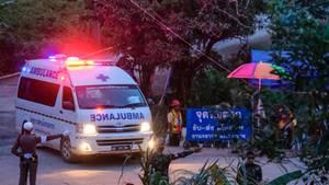 Ein weißer Krankenwagen mit Blau- und Rotlicht biegt ab, während behelmte Polizisten ihm den Weg weisen