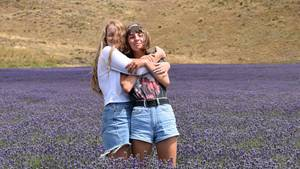 Zwei Mädchen Arm in Arm im Feld