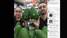 Zwei Supermarktangestellte halten Avozillas hoch, die so groß wie ihr Kopf sind