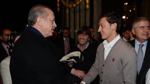 Erdogan und Mesut Özil stehen sich gegenüber, schütteln sich die Hand und lächeln