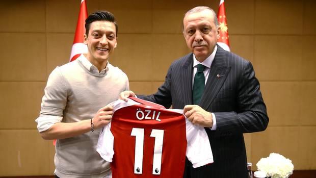 """Links steht Mesut Özil, rechts Erdogan. Gemeinsam halten sie ein rotes Arsenal-Trikot mit """"Özil"""" und der 11 auf dem Rücken"""