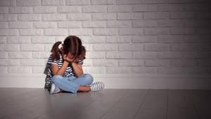Kleines Mädchen sitzt verängstigt auf dem Boden