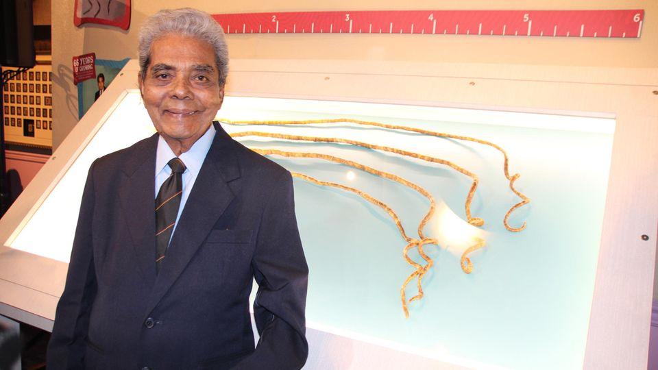 Shridhar Chillal neben seinen in einer Vitrine ausgestellten Fingernägeln