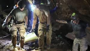Helfer tragen einen Jungen, der auf einer Liege liegt, aus der Tham-Luang-Höhle