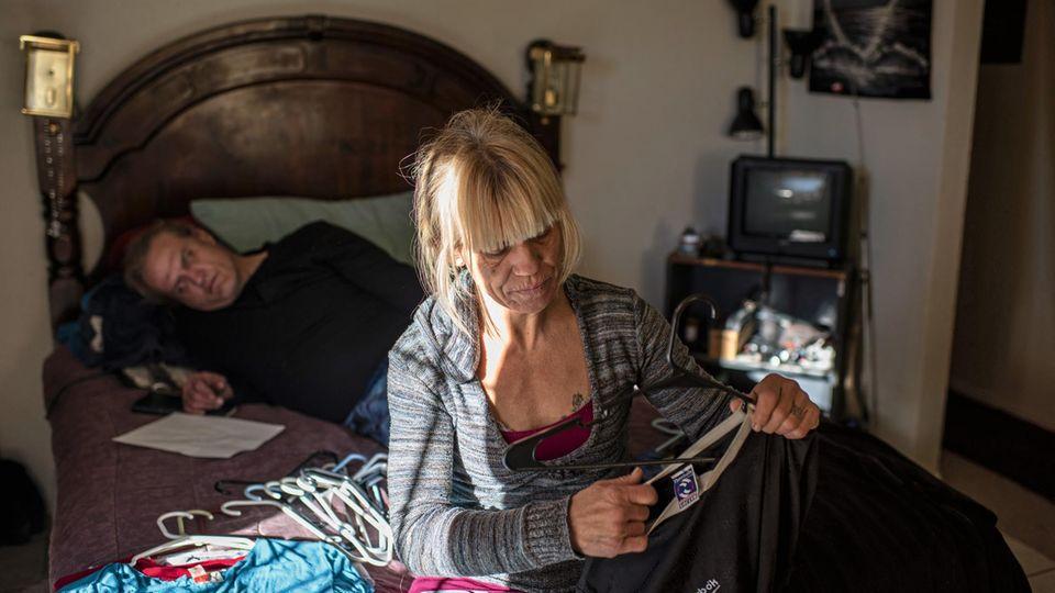 Vom Leben gezeichnet, von den Drogen gezeichnet: Eve, hier 46, ordnet ihre Kleider. Mark, ihr neuer Lebensgefährte, ruht